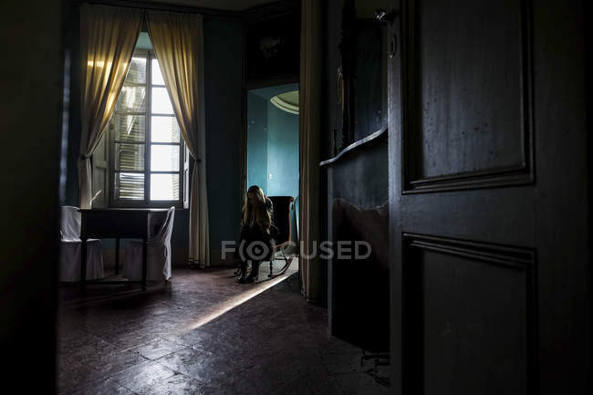 Young woman sitting in a gloomy room — Stock Photo
