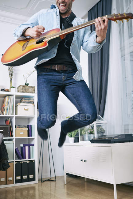 Enthusiastic young man at home playing guitar — Stock Photo