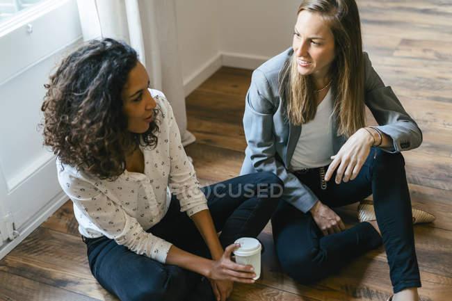 Dois collreagues sentado no chão, conversando e frinking café — Fotografia de Stock