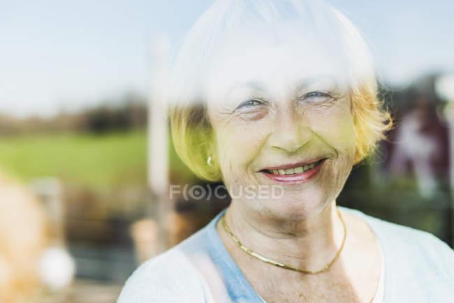 Portrait of smiling senior woman behind windowpane — Stock Photo