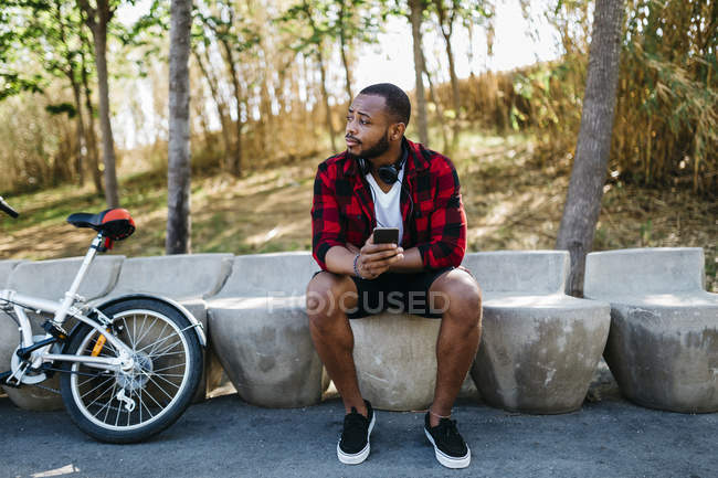 Man sitting with cell phone and bicycle in a park — Stock Photo