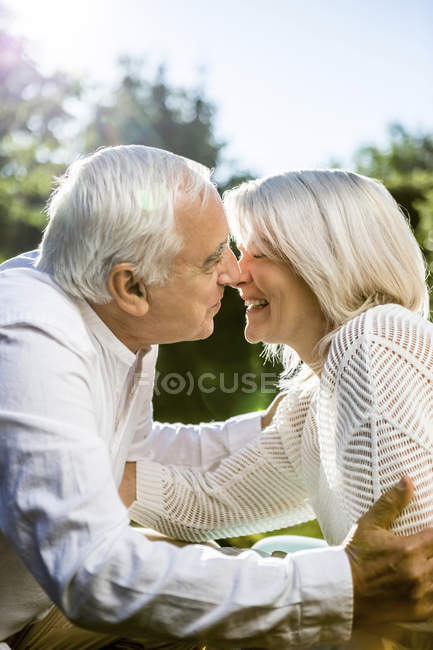 Happy elderly couple kissing outdoors — Stock Photo