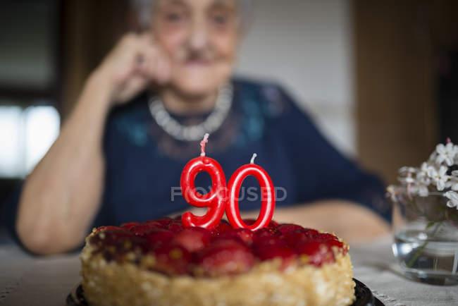 Candles on a birthday cake of a senior woman celebrating her ninetieth birthday — Stock Photo