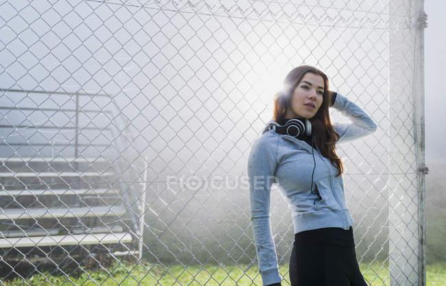Молодая женщина в спортивной одежде прислонилась к сетке проволоки забор — стоковое фото