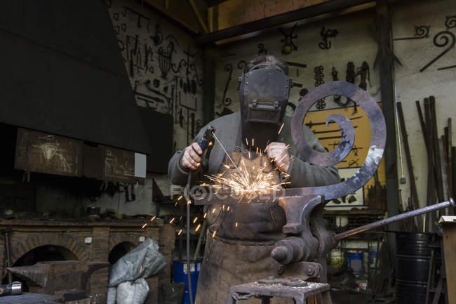 Blacksmith at work in his workshop welding metal detail — Stock Photo
