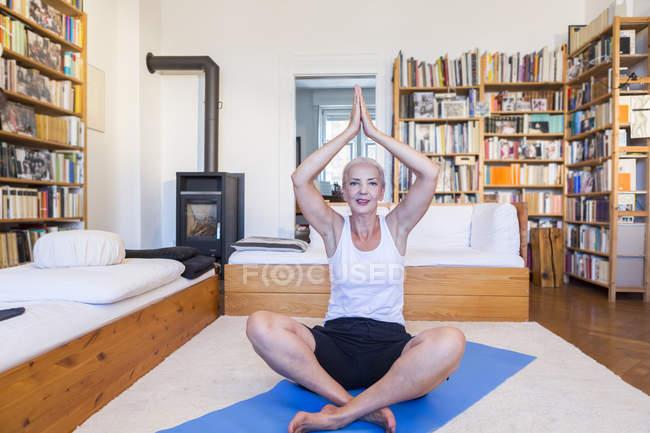 Senior caucasian woman practicing yoga at home — Stock Photo