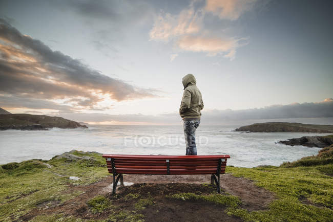 Man wearing hooded jacket standing on bench at the coast looking at distance — Stock Photo