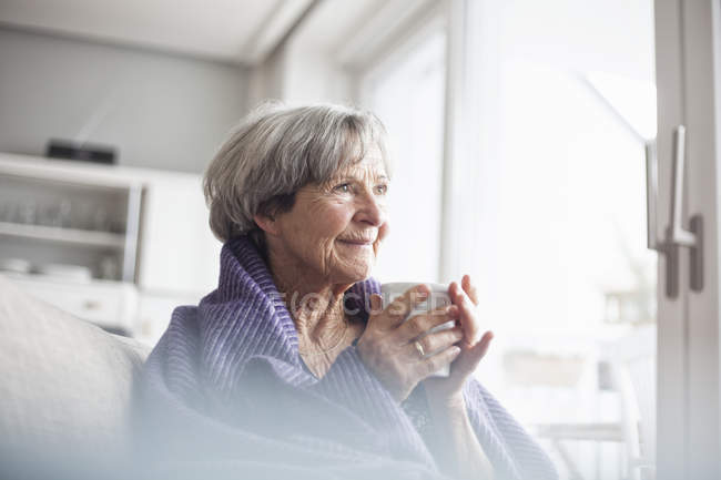 Portrait of happy senior woman sitting on couch at home with cup of coffee — Stock Photo