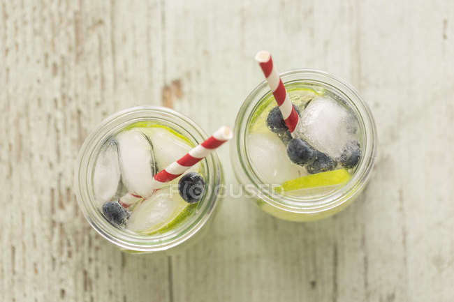 Glasses of infused water with lime, blueberries and ice cubes — Stock Photo