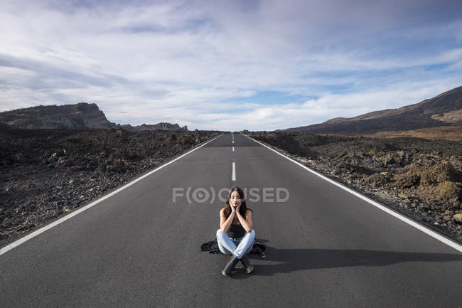 Spain, Tenerife, woman with closed eyes sitting on an empty road — Stock Photo