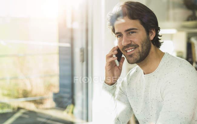 Портрет расслабленного молодого человека, смотрящего в окно во время разговора со смартфоном — стоковое фото