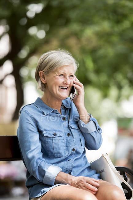 Allegra donna adulta anziana parlando su smartphone contro sfondo sfocato — Foto stock