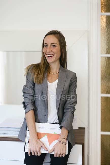 Businesswoman holding files in modern office — Stock Photo