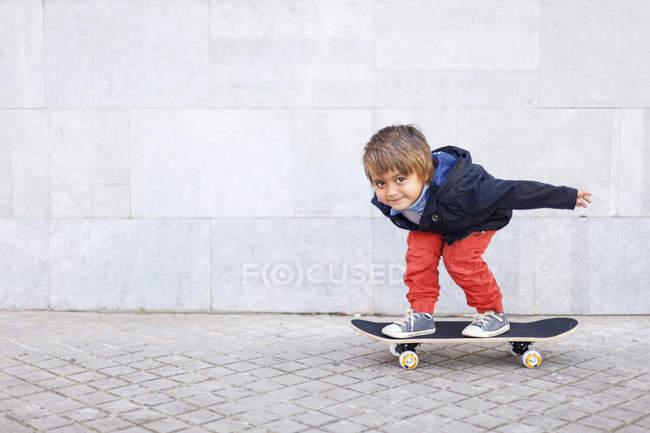 Porträt eines kleinen Jungen, der auf Skateboard balanciert — Stockfoto