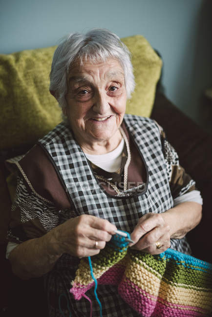 Portrait of smiling senior woman with  knitting — Stock Photo