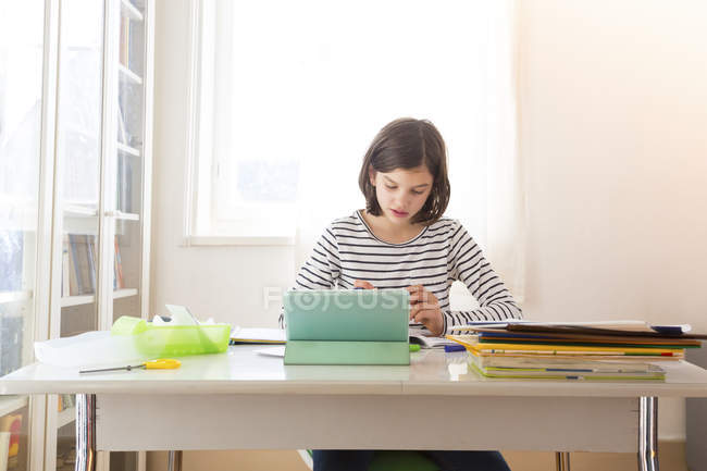 Girl doing homework with tablet at desk — Stock Photo