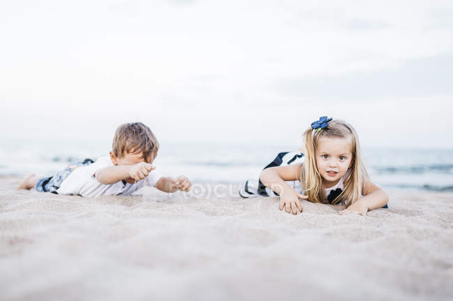 Cute caucasian little brother and sister having fun on sandy beach — Stock Photo
