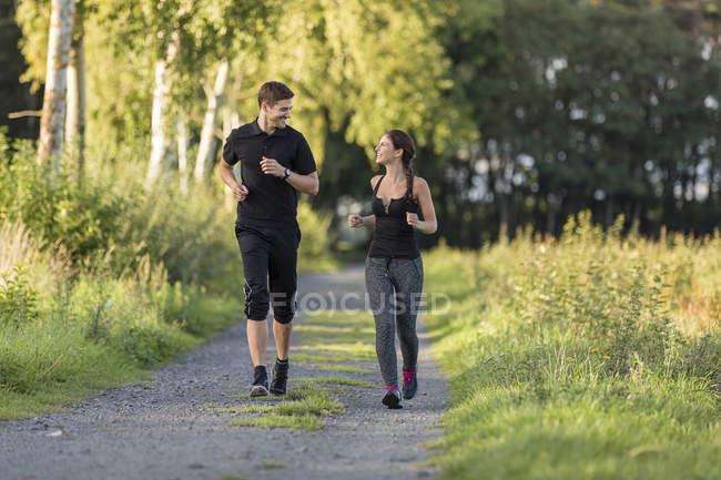 Мужчина и женщина бегают по сельской местности — стоковое фото