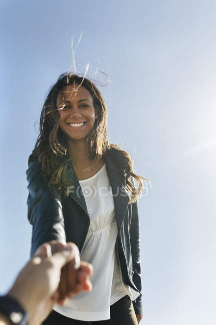 Portrait of smiling young woman with brown hair holding hands in front of sky — Stock Photo