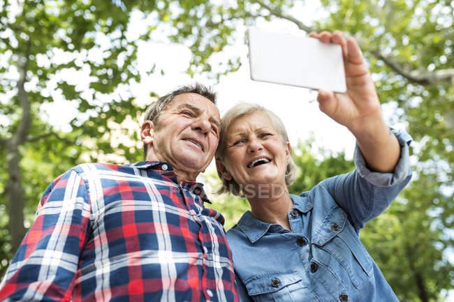 Happy cute senior couple taking selfie on smartphone at park — Stock Photo