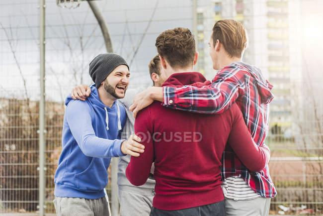 Jóvenes jugadores de baloncesto riendo al aire libre - foto de stock