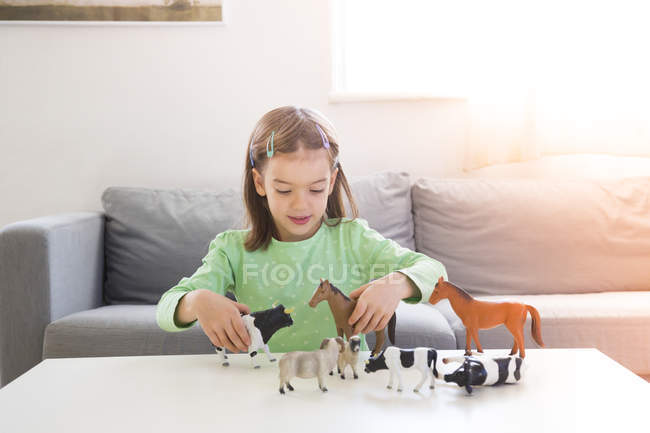 Little girl sitting on couch and playing with animal figurines — Stock Photo