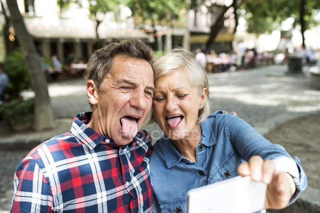 Счастливая милая пожилая пара делает селфи на открытом воздухе — стоковое фото