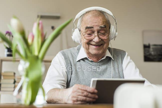 Senior homme avec mini tablet et casques d'écoute à la maison — Photo de stock