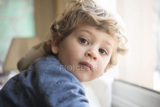 Portrait de petit garçon regardant par-dessus son épaule — Photo de stock