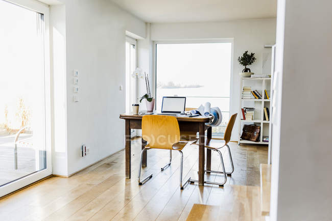 Laptop on wooden desk in an apartment — Stock Photo