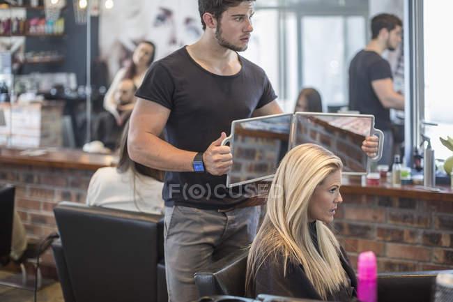 Donna in parrucchiere controllando i capelli allo specchio — Foto stock