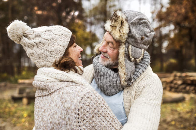 Happy senior couple looking each other in autumnal nature — Stock Photo