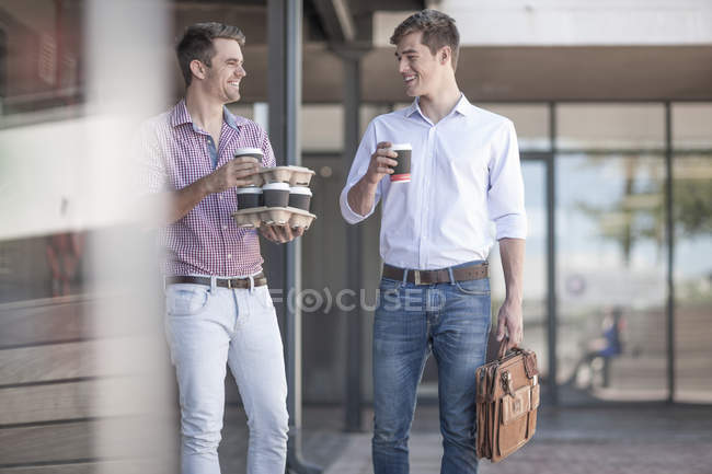 Colleagues talking in the street, holding coffee cups — Stock Photo