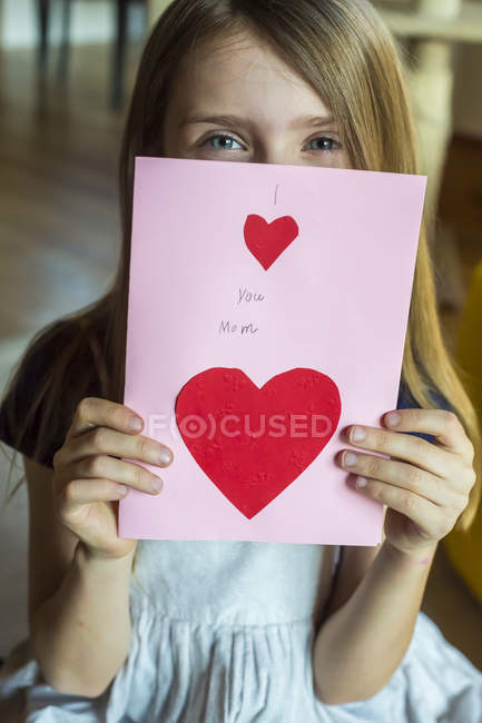 Girl holding self-made mother day card — Stock Photo