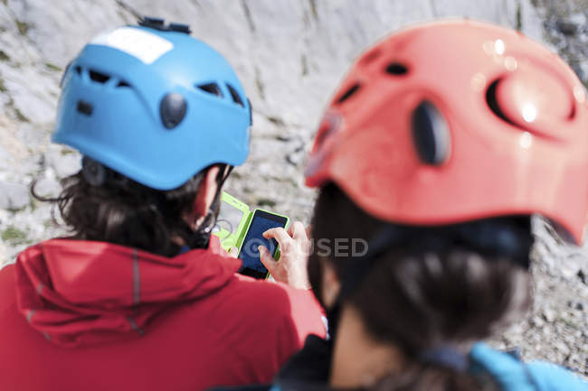 Spain, Picos de Europa, climbers wearing helmets using cell phone — Stock Photo