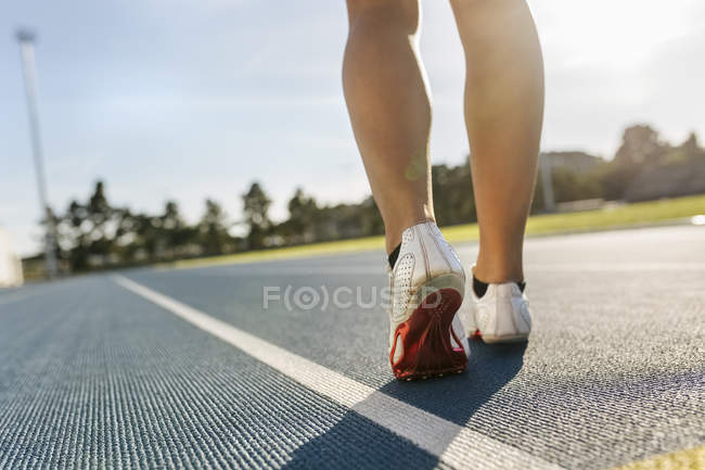 Cropped rear view of sportswoman legs in a race track — Stock Photo