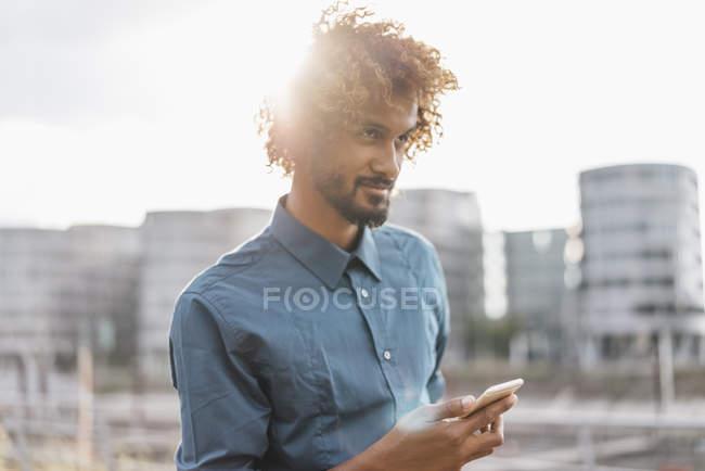 Стильный молодой человек с помощью смартфона в городе — стоковое фото