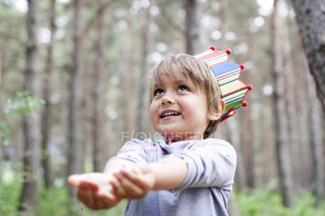 Портрет улыбающегося мальчика в бумажной короне, ловящего конфетти — стоковое фото
