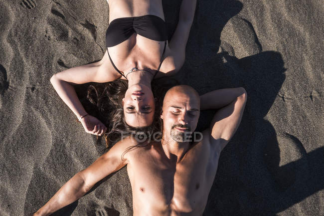 Portrait of couple sunbathing on the beach together — Stock Photo