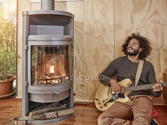 Молодой человек играет электрогитара у камина — стоковое фото