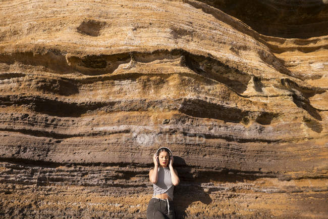 Spain, Tenerife, young woman standing in front of a rock face listening music with headphones — Stock Photo