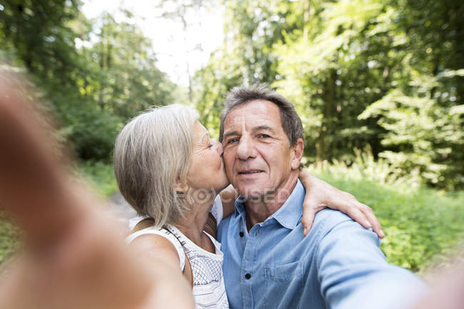 Active cute senior couple hugging, kissing and taking selfie in park — Stock Photo