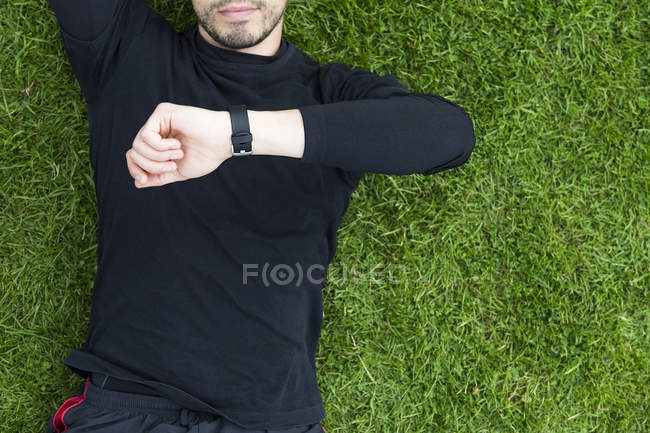 Cropped image of handsome caucasian sporty man lying on grass and looking at watches — Stock Photo