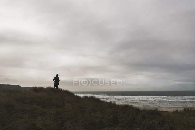 Homem na costa, sob céu nublado — Fotografia de Stock