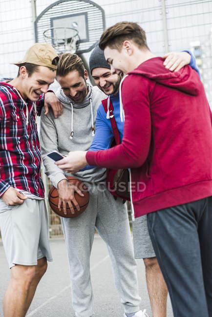 Jovens jogadores de basquete com smartphone rindo em campo — Fotografia de Stock