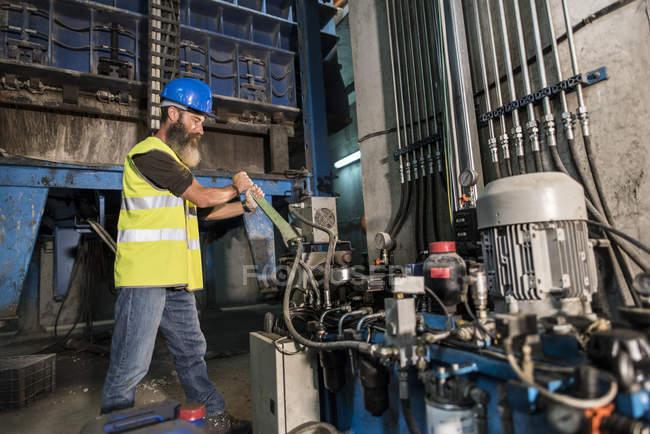 Man in helmet repairing industrial engine — Stock Photo