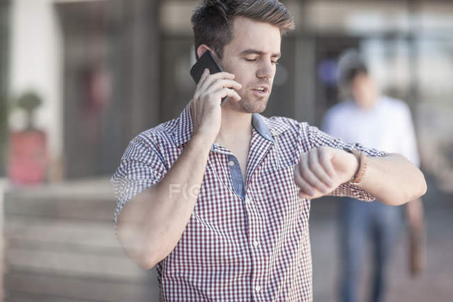 Young man checking time, looking at wrist watch — Stock Photo
