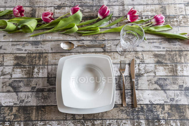 Place setting on table decorated with tulips — Stock Photo