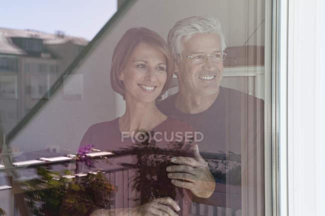 Smiling couple looking through windowpane — Stock Photo