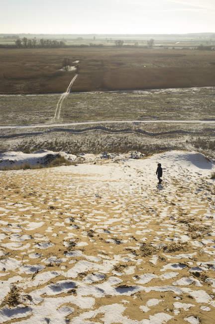Alemanha, Mecklenburg-Vorpommern, perto Doemitz, menino na duna de areia no inverno — Fotografia de Stock